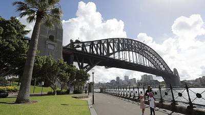 A woman and 2 children walk under the Harbour Bridge in a popular area in Sydney, Australia, Tuesday, April 6, 2021.
