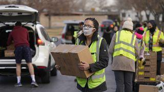 متطوعة تحمل طعاما في مستودع للغذاء في يوتا الأمريكية. 2021/03/11