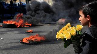 A Syrian boy who sells flowers on the street watches protesters burn tyres to block a main road during a demonstration in Beirut