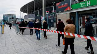 People queue as they arrive at the Stade de France stadium to be vaccinated against COVID-19 in Saint-Denis, outside Paris, Tuesday, April 6, 2021.
