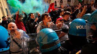 Manifestantes se enfrentan a policías italianos durante una protesta de propietarios de restaurantes y tiendas frente a la Cámara Baja en Roma, el 6 de abril de 2021