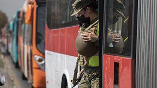 Una soldado sale de un autobús en un puesto de control en Santiago de Chile tras verificar los permisos de tránsito de los pasajeros.