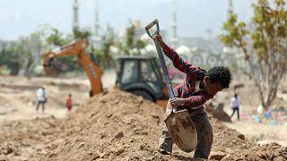 عامل يمني يساعد في حفر قبر لدفن ضحايا وباء كورونا في مدينة تعز في اليمن. 03/04/2021