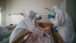 Védőfelszerelést viselő orvosok hasra fordítanak egy beteget a fővárosi Honvédkórház koronavírus- osztályán