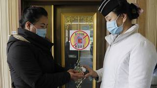 A staff member, right, of the Pongnam Noodle House disinfects the hands of a woman coming into its restaurant in Pyongyang, North Korea.