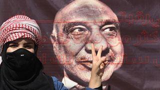 متظاهرة تقف أمام صورة رئيس الوزراء العراقي السابق عادل عبد المهدي في ساحة التحرير في بغداد. 2020/10/01