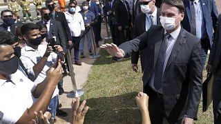 Wearing a mask, Brazil's President Jair Bolsonaro greets people in a neighborhood of Brasilia, Monday, Apr. 5, 2021.