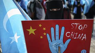 A protester from the Uyghur community holds up an anti-China placard during a protest in Istanbul.
