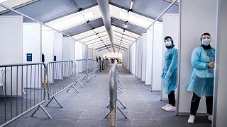 Miembros del personal esperan para administrar las pruebas, en el nuevo centro COVID-19 en Faelledparken, Copenhague, el lunes 29 de marzo de 2021.