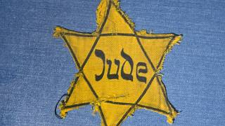 In this Wednesday, Jan. 22, 2014 file photo, the Yellow Star badge of Heinz-Joachim Aris (Dresden 1941) reading 'Jew' is displayed at the Military History Museum in Dresden.