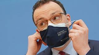 Jens Spahn, Federal Minister of Health, takes off his mouth-nose protection at the Federal Press Conference in Berlin, Germany, Thursday, April 1, 2021.