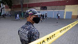 Un poliziotto controlla l'accesso a un quartiere di Caracas chiuso a causa del Covid-19, 7 aprile 2021