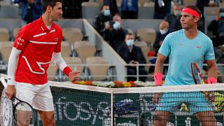 Novak Djokovic, a la izquierda, y Rafael Nadal se miran antes del partido final del torneo en el estadio Roland Garros en París, Francia, el 11 de octubre de 2021.
