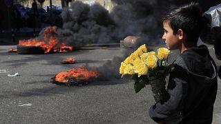 Un bambino siriano guarda i manifestanti che bruciano pneumatici per bloccare una strada principale durante una manifestazione a Beirut
