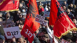 """Supporter of VETEVENDOSJE (Self-Determination) political party holds a slogan reading in Albanian """" All and Straight"""" during the closing electoral rally in capital Pristina."""