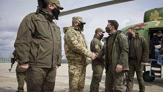 Ukrainian President Volodymyr Zelenskiy shakes hands a soldier as he visits the war-hit Donetsk region, eastern Ukraine, Thursday, April 8, 2021.