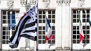 """Le """"Gwenn ha Du"""", le drapeau breton et des drapeaux français flottant devant l'hôtel de ville de Nantes, dans l'ouest de la France, le 20 février 2021"""