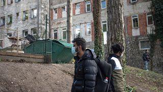 Migrantes caminan fuera del campamento de Borici en Bihac, Bosnia, el 7 de abril de 2021.
