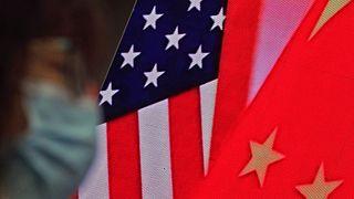 امراة تمشي حذو شاشة يظهر عليها العلمان الأمريكي والصيني بينما تستمع إلى خطاب وزير الخارجية الصيني. 2021/02/22