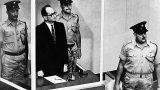 أدولف أيخمان يقف في قفص زجاجي، محاطا بحراس، في قاعة محكمة القدس أثناء محاكمته عام 1961
