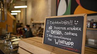 "A banner reading in Spanish: ""Welcome, we cannot serve in the bar. Sit down and we communicate by WhatsApp"" at La Francachela restaurant in Madrid, Spain, March 26, 2021."