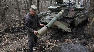 Ukrainischer Soldat untersucht einen Panzer