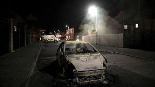 Les restes d'une voiture calcinée après les heurts à Belfast (Irlande du nord), le 09/04/2021