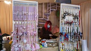 An employee, wearing a face mask to curb the spread of the coronavirus, works behind decorated candles for the Orthodox Easter