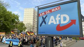 This picture taken May 1, 2019 shows AfD supporters walkin along a party elections poster in Erfurt, Germany.