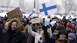A group of people hold placards during a protest against the Finnish government's regulations to fight the coronavirus pandemic in Helsinki, March 20, 2021.
