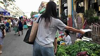 woman delivers the Molotov newsletter to people in a market