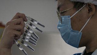 Sinovac-vakcinákat vizsgál egy dolgozó Pekingben 2020. szeptember 24-én