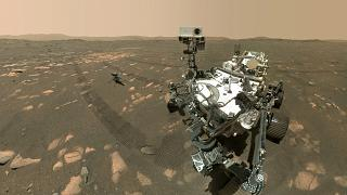 A selfie by the Perseverance Mars rover with the Ingenuity helicopter a few metres behind it.