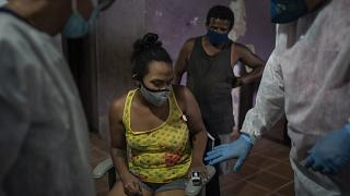 Mobile Emergency Care Service (SAMU) worker Elias Anjo, right, checks a patient suspected of having COVID-19 at her house in Duque de Caxias, Brazil.