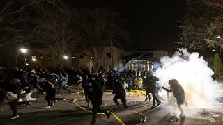 People run as police attempt to disperse the crowd at the Brooklyn Center Police Department, late Sunday, April 11, 2021, in Brooklyn Center, Minn.
