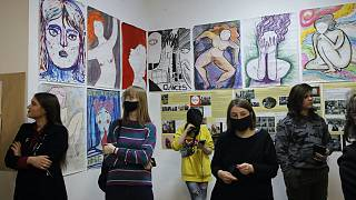 Visitors look at the exhibition of Yulia Tsvetkova's paintings in St. Petersburg, Russia, Saturday, April 10, 2021.