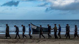 ARCHIVO, en esta foto de archivo del martes 20 de octubre de 2020, migrantes de Marruecos caminan escoltados por la Policía española tras llegar a Canarias.