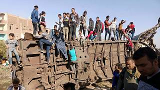 Egyptians gather around mangled train carriages at the scene of a train accident that killed at least 18 people and wounded 200 others including children, in Sohag, Egypt