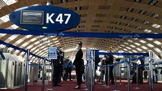 Az Air France földi személyzetének tagjai várják az utasokat a Charles de Gaulle repülőtéren - MTI