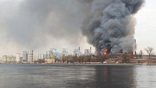 Fire burning in Nevskaya Manufaktura building, emergency vehicles on Neva river's bank