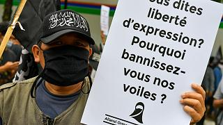 متظاهرون مسلمون يرفعون لافتات خلال مظاهرة مناهضة للرئيس الفرنسي إيمانويل ماكرون.
