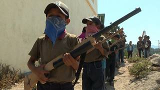 Child wearing a mask holds a replica rifle