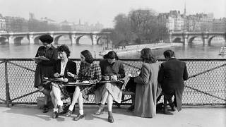 Young women draw on the Pont des Arts in Paris on the first warm spring days. March 1946