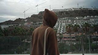Un migrante mira el paisaje desde el balcón del hotel que le acoge