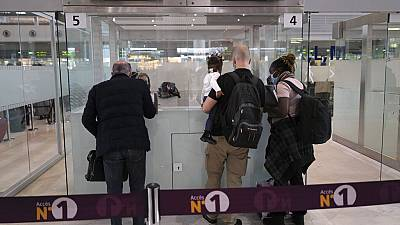 Passengers are checked by French police officers before boarding a flight at Paris Charles de Gaulle Airport in February 2021