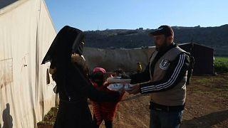 توزيع وجبات طعام على سكان مخيم في إدلب شمال سوريا
