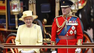 Britain's Queen Elizabeth II, and Prince Philip take a salute as the Guards march past outside Buckingham Palace on June 16, 2012.