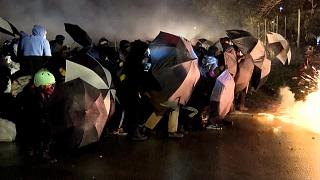 Protesters holding umbrellas as shields