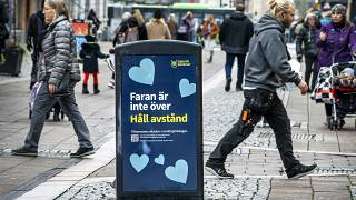 """People walk past a bin with a sign reading """"The danger is not over. Keep your distance"""" in a pedestrian street in central Uppsala, Sweden. October 21, 2020."""