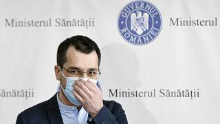 Romania's former health minister Vlad Voiculescu adjusts his mask during a press conference in Bucharest.